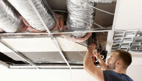 Save Download Preview Male technician measuring voltage during repair of industrial air conditioner indoors