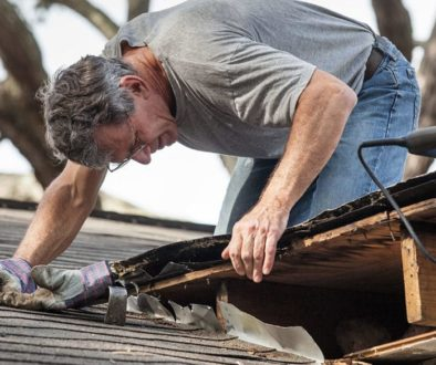 man using crowbar and saw to remove rotten wood from leaky roof decking